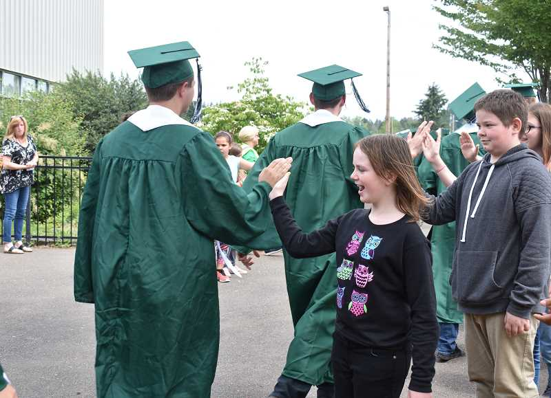 ESTACADA NEWS PHOTO: EMILY LINDSTRAND - Graduating Estacada High School seniors triumphantly march down the halls of River Mill Elementary School during the districts annual grad walk on Friday, June 8.