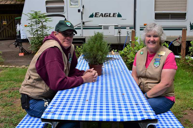 ESTACADA NEWS PHOTO: EMILY LINDSTRAND - Hugh and Lynn Fulton sit on the picnic bench outside of their RV at Milo McIver State Park. After retiring from teaching, the Fultons became full time camp hosts, visiting parks across the country.