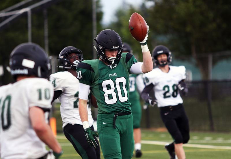 TIMES PHOTO: DAN BROOD - Green tight end Fletcher Ahl (80) holds up the football after his second touchdown reception during Saturdays Chicken and Bean Bowl.