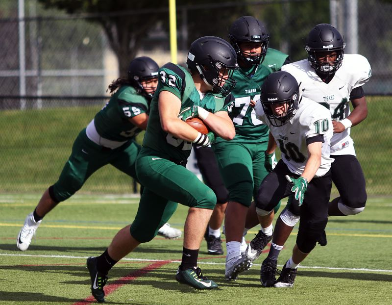 TIMES PHOTO: DAN BROOD - Mitchell Cross carries the ball for the Green team, on a 2-point conversion run, during the Tigard Chicken and Bean Bowl.