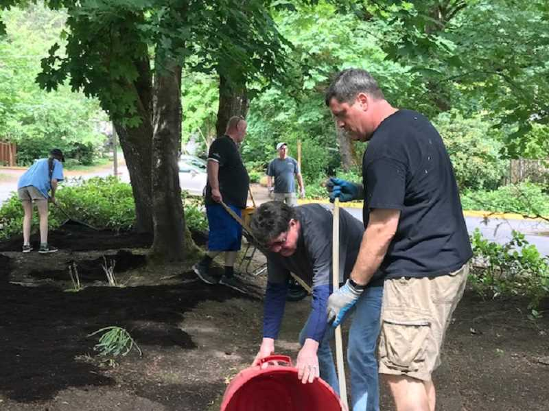 SUBMITTED PHOTO: WINDERMERE REALTY GROUP - Roy Hovey and Todd Gydesen work as a team to clean up weeds and other yard debris cleared from the beds surrounding the Lake Oswego Adult Community Center.