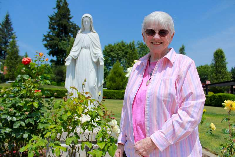 REVIEW PHOTO: SAM STITES - Sister Marilyn Barry stands with a statue of the Blessed Virgin Mary outside the Parish Center of Our Lady of the Lake Catholic Church in downtown Lake Oswego.