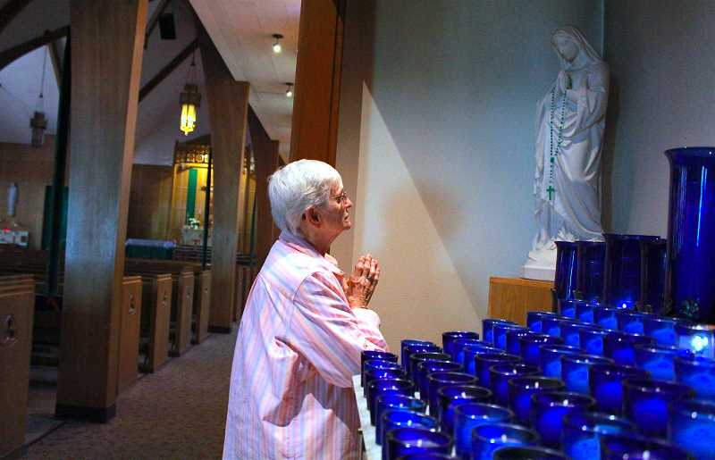 REVIEW PHOTO: SAM STITES - Flickering votive candles light the devotional area of Our Lady of the Lake as Sister Marilyn prays to the Blessed Virgin Mary.