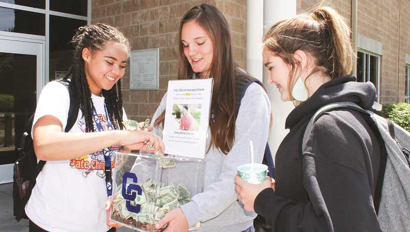 HOLLY SCHOLZ/CENTRAL OREGONIAN  - Crook County High School students collected change from classmates Tuesday afternoon for Vicente Ramirez, who needs a kidney transplant. Pictured left to right, junior Lyndee Walker, who will be senior class president, stuffs dollar bills into the bank as freshman Liz Barker and freshman Chloe Arnold look on.