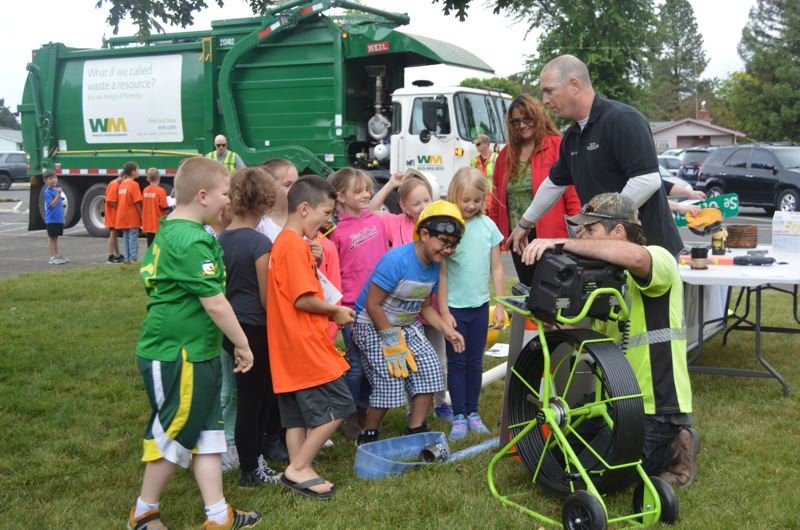 SPOTLIGHT PHOTO: NICOLE THILL-PACHECO - Scappoose Public Works employees Tom Jadrnak and Doug Nassimbene show students how a sewer scope camera works.