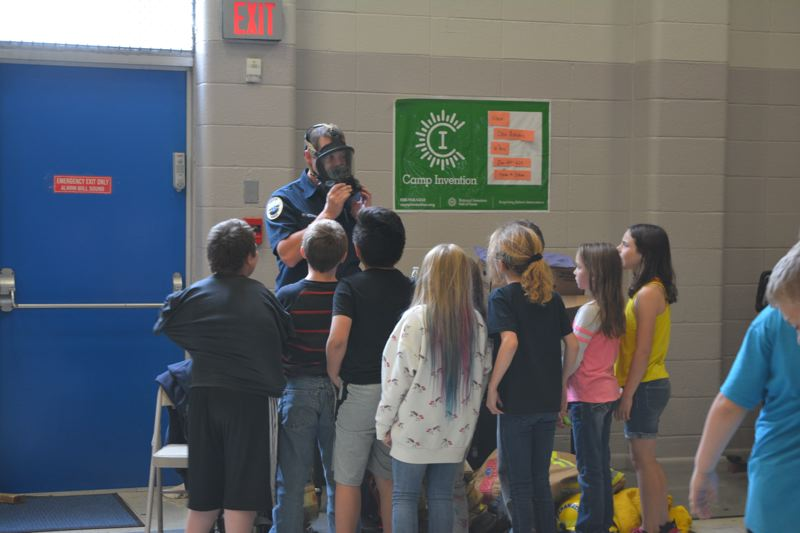 SPOTLIGHT PHOTO: COURTNEY VAUGHN - Aaron Peterson with Columbia River Fire & Rescue demonstrates how firefighters wear masks to protect themselves from smoke inhalation when battling blazes. Peterson showed students firefighter uniforms and talked about his job during a career expo held at Grant Watts Elementary School Wednesday.