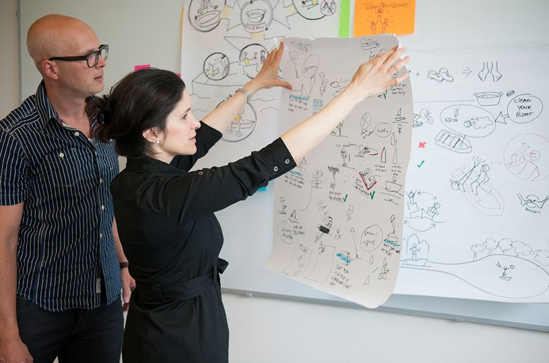 COURTESY: XPLANE - XPLANE staff with visualizations in the XPLANE office in Portland. Good cartooning skills and deft use of Post-It notes are a key part of the business of focusing corporate minds and conveying information about change.
