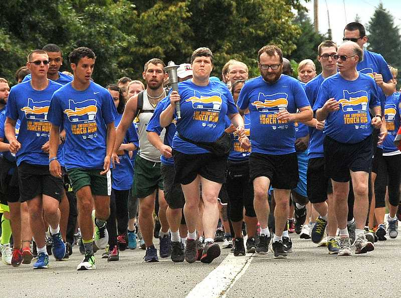 REVIEW FILE PHOTO: VERN UYETAKE - Special Olympics Oregon athletes and law enforcement officials jog through Lake Oswego on one leg of the 2017 Law Enforcement Torch Run. For more than 30 years, the relay has finished at the State Summer Games, but that competition was canceled Monday because of financial problems.