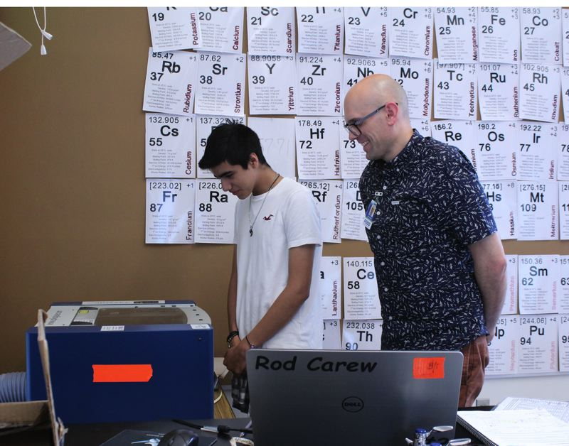 STAFF PHOTO: OLIVIA SINGER - FGHS freshman Jose Botello stayed after school to use the Epilog Laser with help from science teacher John Worst.