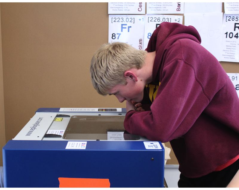 STAFF PHOTO: OLIVIA SINGER - A Forest Grove High School student watches as the Epilog Laser engraves his design on a wooden tag.
