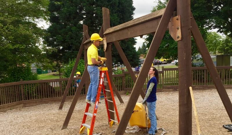 OUTLOOK PHOTO: MATT DEBOW - Troutdale City Manager Ray Young and Elizabeth Welch help to take apart a swing at Imagination Station on Saturday, June 16.