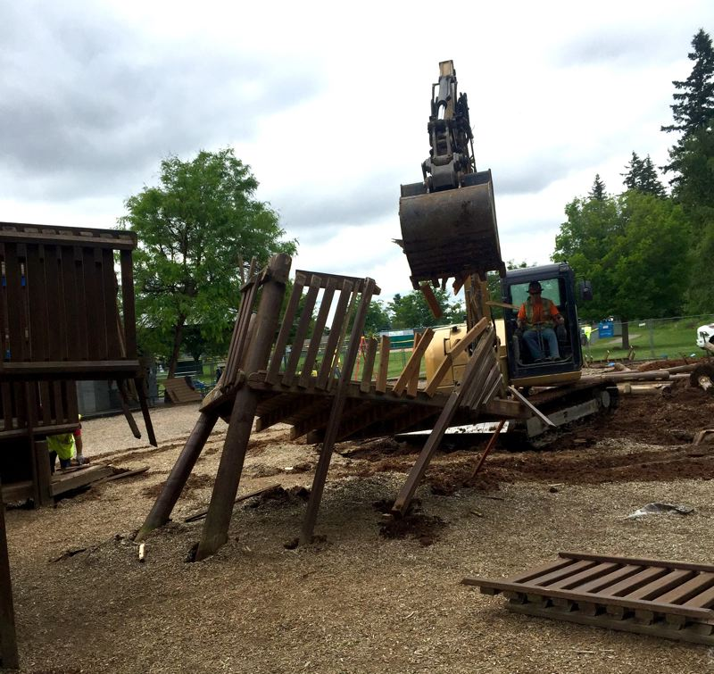 OUTLOOK PHOTO: MATT DEBOW - A backhoe demolishes a play structure at Imagination Station on Saturday, June 16. The playground was torn down about two years after a third of the playground was burned by a fire.