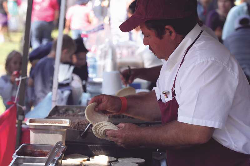 INDEPENDENT FILE PHOTO - A vendor at last year's Hop Festival prepares food for hungry patrons.