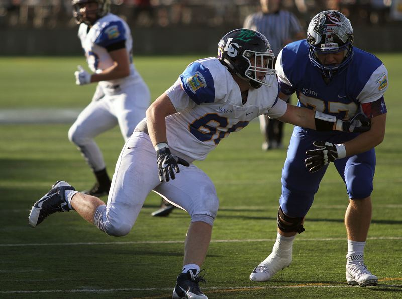 REVIEW PHOTO: MILES VANCE - Lake Oswego graduated senior Shawn Elliott rushes the quarterback for the North team during its 24-7 win over the South in the annual Les Schwab Bowl on Saturday at Hillsboro Stadium.