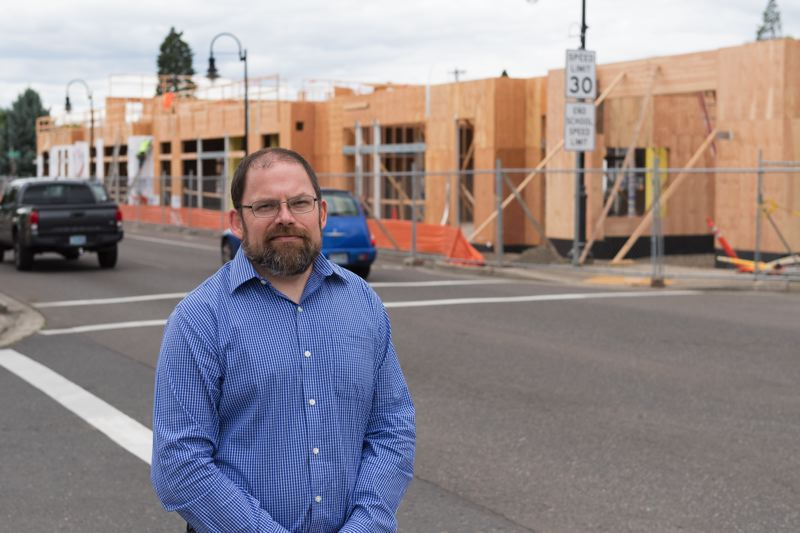 STAFF PHOTO: CHRISTOPHER OERTELL - Ryan Wells stands in front of Cornelius Place, a three-story building under construction at the corner of North Adair Street and 14th Avenue in Cornelius. Once complete, the building will house an expanded Cornelius Public Library and more.