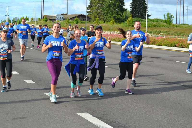 COURTESY PHOTO - Emily Heller, Memory Condren, Katie Heller, Sadie Hansen and Nathan Cook are full of smiles just one mile into this year's 13.1-mile Helvetia Half-Marathon.