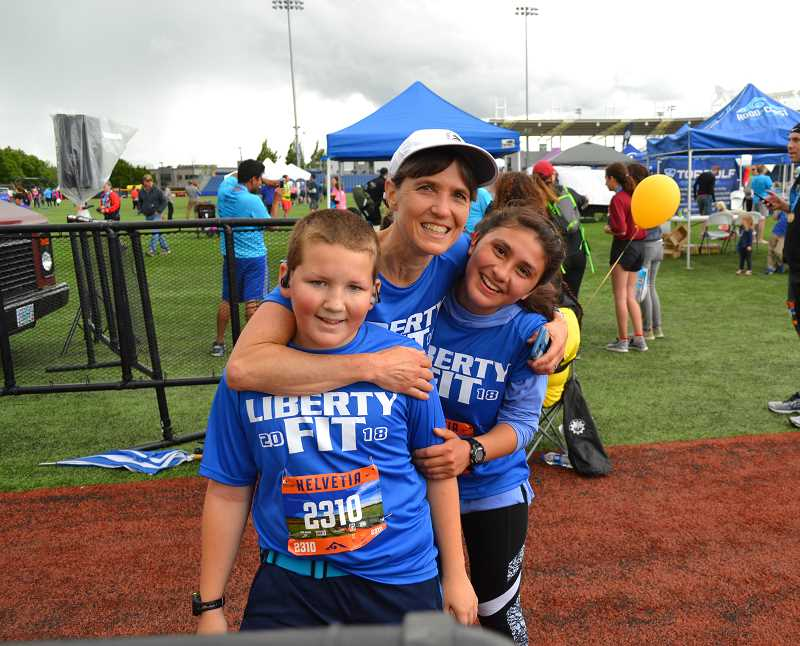COURTESY PHOTO - Liberty Fit coach Laurie Jenkins celebrates with Zeke Winchester and Emerald Koeppel after the trio crossed the finish line together Saturday, June 9, at the Helvetia Half-Marathon at Hillsboro Stadium. The program, which ended its 12th season, draws close to 100 students of varying abilities to train and complete either the 13.1-mile race or the companion 10K, with Liberty and other HSD staff, family and community members also taking part.