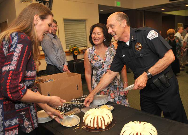 REVIEW PHOTO: VERN UYETAKE - Lake Oswego Police Chief Don Johnson and his wife Denise help cut the cake at his retirement party Monday at City Hall. Johnson leaves the department on July 1 after a 39-year career that included seven years in Lake Oswego.