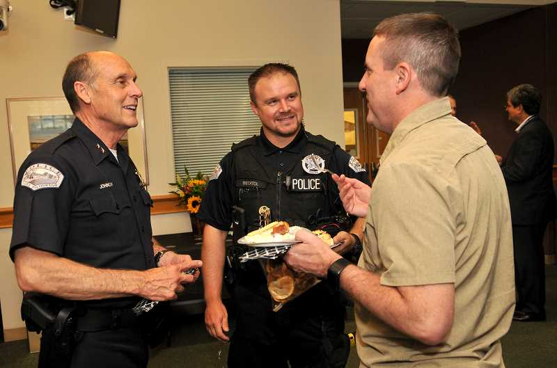 REVIEW PHOTO: VERN UYETAKE - Police Chief Don Johnson chats with the LOPD's Vaughn Bechtol and Jay Weitman at Johnson's retirement party, which drew dozens of well-wishers to City Hall.