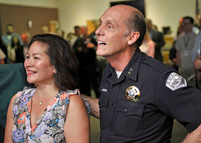 REVIEW PHOTO: VERN UYETAKE - Police Chief Don Johnson and his wife Denise watch a farewell video filled with best wishes from city and school officials, first responders and community members.