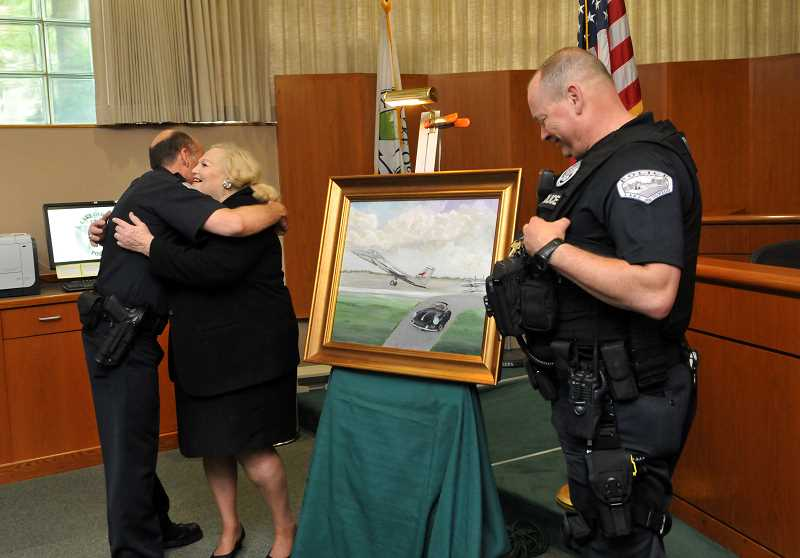 REVIEW PHOTO: VERN UYETAKE - Police Chief Don Johnson hugs Jerry Ghiglieri after accepting the painting she created for him as a going-away gift. LOPD Lt. Doug Treat (right) helped Ghiglieri with the presentation.