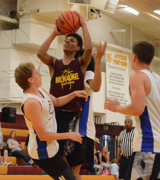 PAMPLIN MEDIA: DAVID BALL - Milwaukies Keshawn Myles draws a foul in the lane during the third quarter of the teams 69-68 overtime win over Gresham.