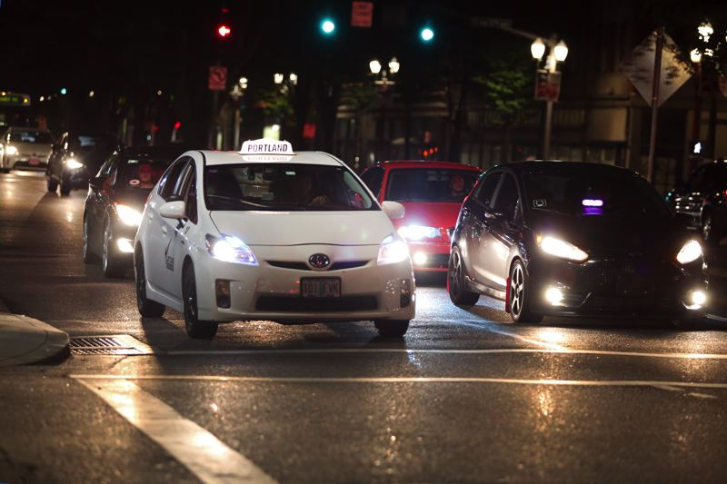 TRIBUNE PHOTO: JESSIE DARLAND  - A mix of Ubers, Lyfts, taxis, and personal vehicles line up at a stoplight last Saturday night near Old Town/Chinatown.