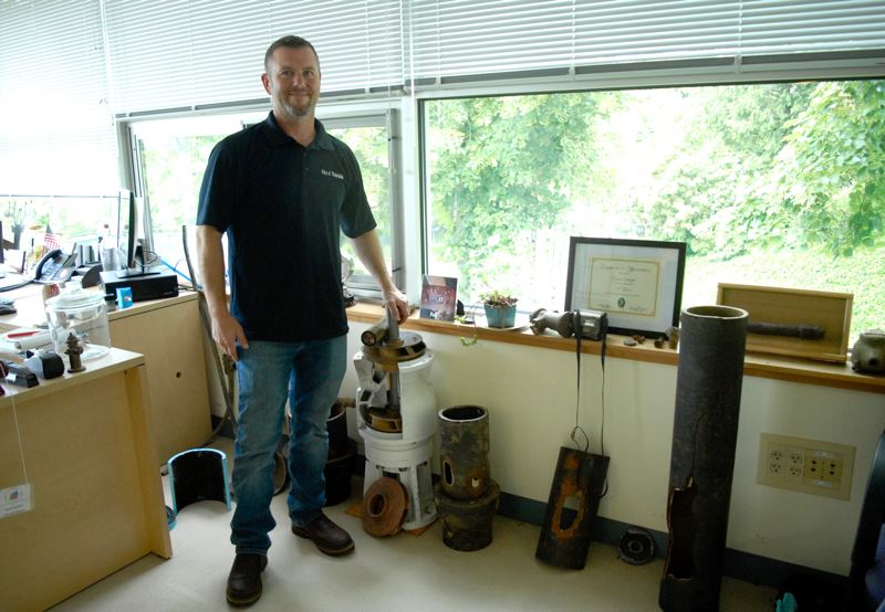 OUTLOOK PHOTO: MATT DEBOW - Troutdale Public Works Superintendent David Schaffer stands next to several water-system-related items in his office.