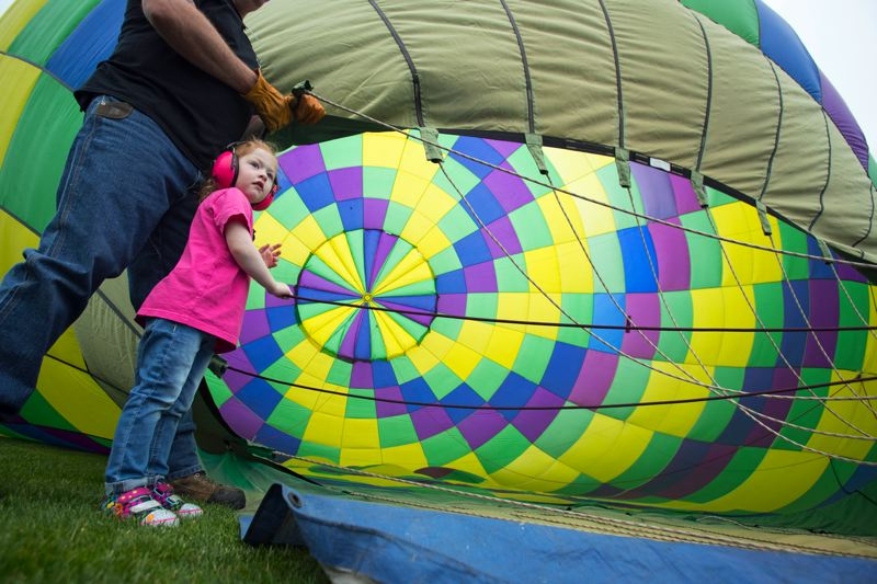 TIMES PHOTO: JAIME VALDEZ - Daphne Lucia, 3, 'crews' for balloonist Cheryl Isaac as they team inflates the balloon Friday morning.