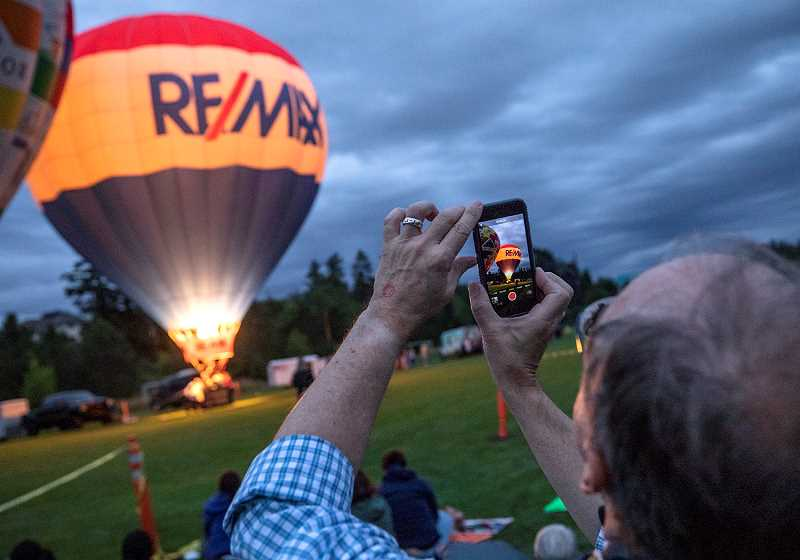 THE TIMES: JONATHAN HOUSE - Onlookers take photos of the night glow at the Tigard Festival of Balloons Friday night.