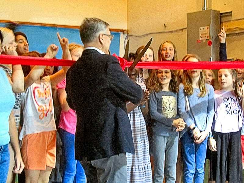 ERIC NORBERG - Graduating fifth graders joined Executive Director Glen Gilbert in the cutting of the ceremonial ribbon with the big scissors to inaugurate use of the new solar panel roof at Tucker Maxon School. With the ribbon cut, Gilbert and many of the students reached for the big red switch on the power panel nearby, to put the new solar panels online.