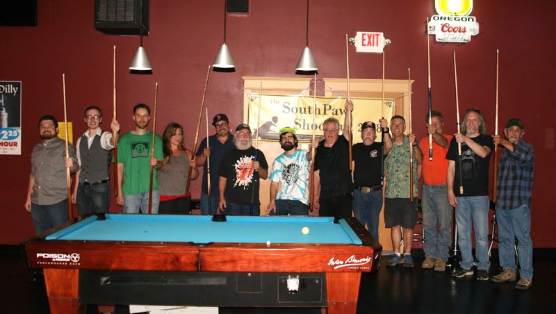 PHOTO BY: BILLYBDESIGN - Thirteen of the 16 participants in the inaugural Southpaw Shoot-out raise their pool cues in celebration at the Midway Pub in Oregon City.