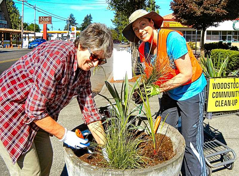 ELIZABETH USSHER GROFF - Ingrid Mather and Beth Iversen replant a pot on the Wooodstock Boulevard south of the BiMart parking lot. They remind that volunteers are needed to help water the containers in dry weather.