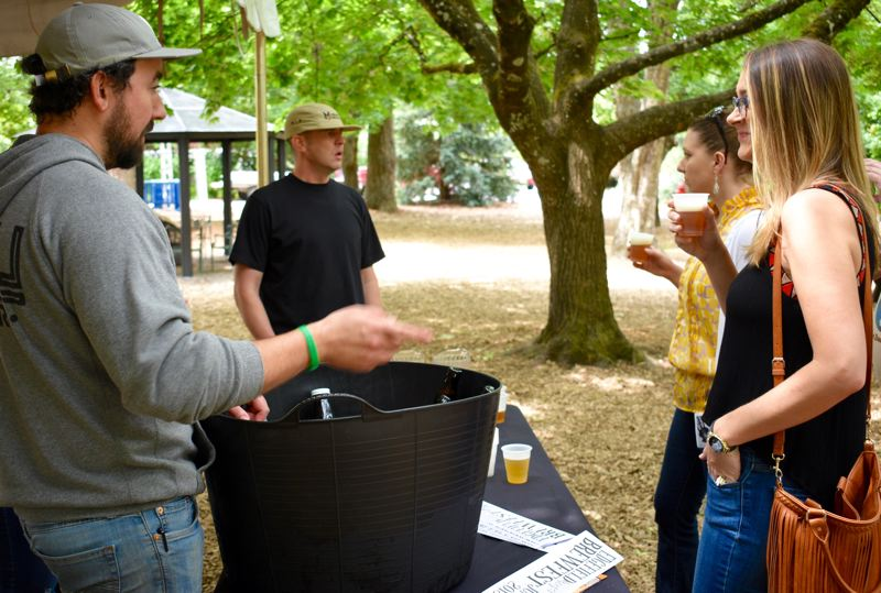 OUTLOOK PHOTO: MATT DEBOW - Foreground: Jason Barbee, from Level Brewing, speaks with Holly Amlin over a beer on Thursday, June 21 during a preview event for the inaugural Edgefield brewfest on Saturday, June 30.  Background: Eric Banzer-Lausberg, from Migration Brewing, talks with Andi Prewitt.