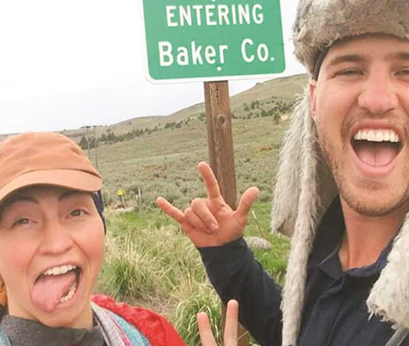 PHOTO COURTESY OF KOLTON RACKHAM AND AMANDA AUTREY  - Amanda Autrey and Kolton Rackham have taken many pictures on their journey. The couple take a selfie as they enter Oregon's Baker County.