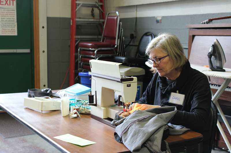 REVIEW FILE PHOTO: PATRICK MALEE - Carol Bryck hems pants at a recent repair fair in West Linn. On Saturday, volunteers will help Lake Oswego residents fix and mend everything from clothing and toys to bicycles and small appliances.