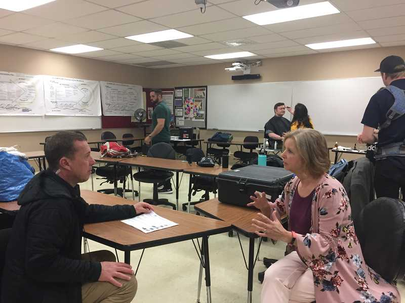 COURTESY PHOTO: TAMI BADINGER - North Marion Middle School teachers Peggy Boorman, pictured right talking with a producer, and Justin Jacobs, who gets his makeup done in the background, were interviewed and featured in the Subaru commercial.