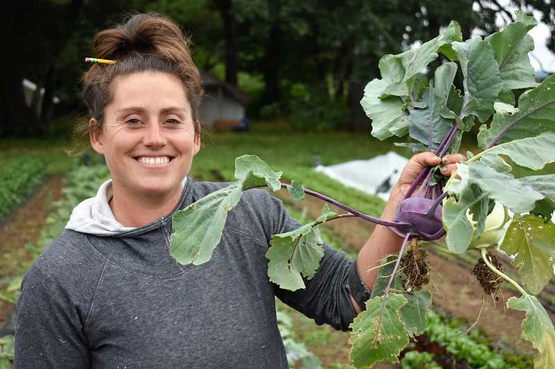 ESTACADA NEWS PHOTO: EMILY LINDSTRAND - Jennifer Van Wey shows off a kohlrabi at Quackenbush Farm. She described the vegetable as tasting 'like sweet broccoli.'