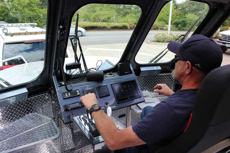 REVIEW PHOTO: ANTHONY MACUK - LOFD Driver-Engineer Brad Hensley demonstrates the new boat's controls. Instead of a wheel, the boat is controlled by a stick for left and right turns.