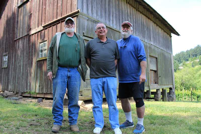 REVIEW PHOTO: SAM STITES - Steve Cook (from left), Mark Browne and Rick Cook pose for a photo outside the 150-year-old barn on the Cook family's property in Stafford.
