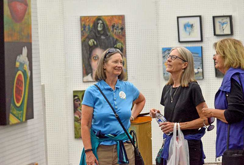 REVIEW PHOTO: VERN UYETAKE - Cathy Olson (from left), Norene Quam and Barb Petrick discuss art on display at the Open Show, which featured the work of emerging and established artists.