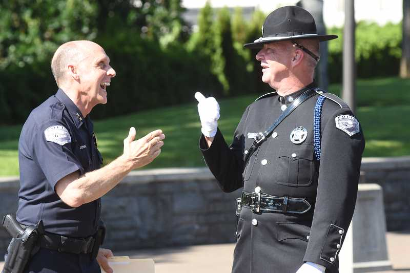 SUBMITTED PHOTO: DAVE ARPIN - Chief Don Johnson jokes with LOPD Lt. Darryl Wrisley following the swearing-in ceremony for new Police Chief Dale Jorgensen last week in Millennium Plaza Park. Johnson officially retires July 1 after seven years with the department.