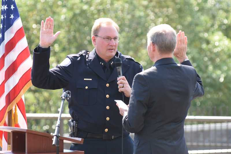 SUBMITTED PHOTO: DAVE ARPIN - City Manager Scott Lazenby admisters the oath of office to new Lake Oswego Police Chief Dale Jorgensen in a special ceremony held last week in Millennium Plaza Park.