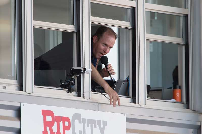 STAFF PHOTO: CHRISTOPHER OERTELL - Hillsboro Hops announcer Rich Burk leans out the window of the press box at Ron Tonkin Field to sing 'Take Me Out To The Ball Game,' during the Hops game June 24.