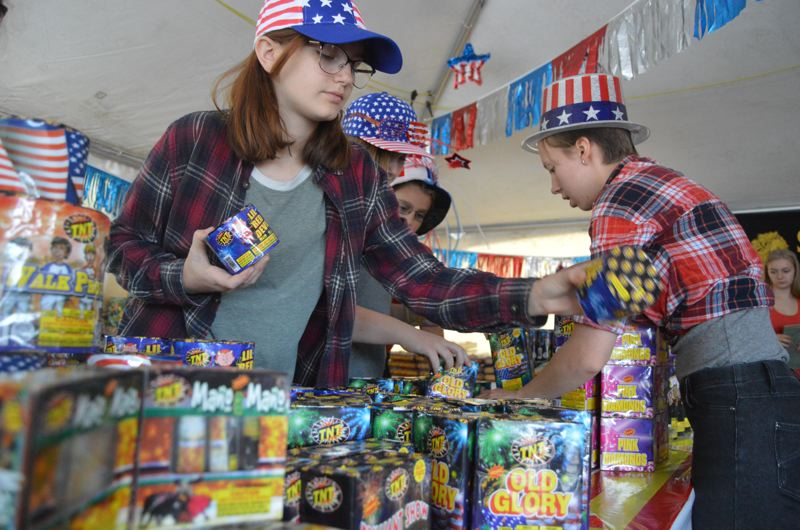 SPOTLIGHT PHOTO: NICOLE THILL-PACHECO - Members of the St. Helens Band Patrons group sell fireworks in the parking lot of Walmart as a program fundraiser leading up to Independence Day, and will be selling a variety of items every day from 9 a.m. to 9 p.m. Pictured here on June 28,  from left to right, Sadie McGuire, Jenna Cook, Caleb Polvogt, and Kitara Church, all members of the St. Helens band, color guard and choir programs, help set up fireworks displays in preparation for the sales.