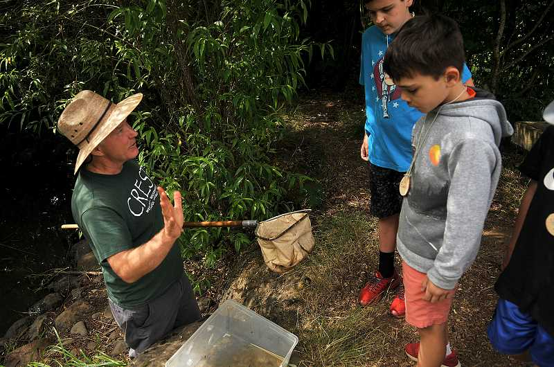 SPOKESMAN PHOTO: VERN UYETAKE  - CREST Director Bob Carlson shows kids how to dip for tadpole in the stream.
