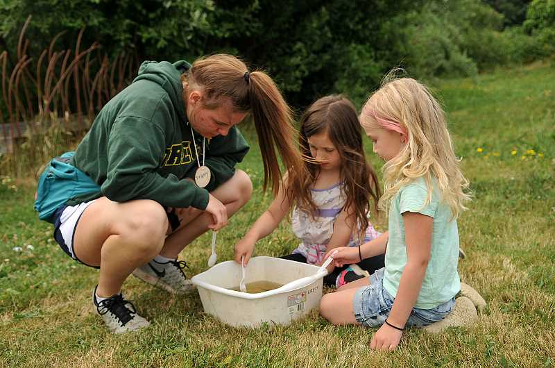 SPOKESMAN PHOTO: VERN UYETAKE  - From left, Delaney Dougherty, Maggie Boschielo and Sadie Jankovich check out tadpoles.
