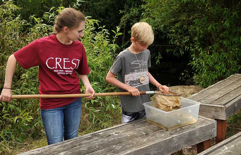 SPOKESMAN PHOTO: VERN UYETAKE  - Camp coordinator Emma Steffen helps Gabe Jankovich catch tadpoles.