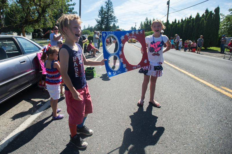 OUTLOOK FILE PHOTO - Kids use their ingenuity to score more candy from parade floats during last years Fourth of July parade in Corbett.