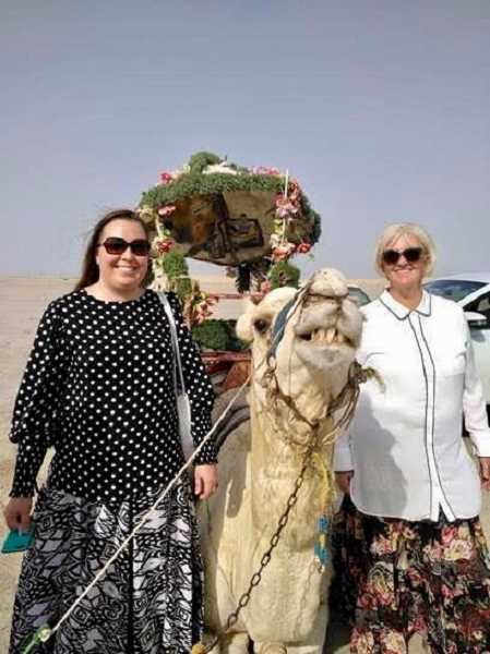 CONTRIBUTED PHOTO: LOIS LENTS - Dominique Kuzmaak and Sheryl Vanderwalker stand with one of the camels they got to ride at the end of their trip.